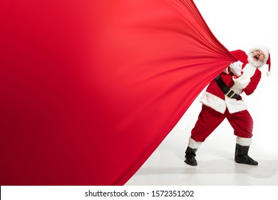 Santa Claus pulling huge bag full of christmas presents isolated on white background. Caucasian male model in traditional costume. New Year 2020, gifts, holidays, winter mood. Copyspace for your ad.
