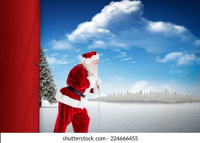 Santa claus pulling rope against fir tree in snowy landscape