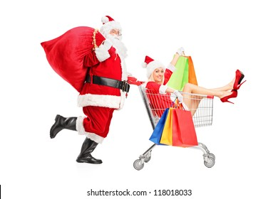 Santa Claus pushing a woman with shopping bag in a push cart isolated on white background