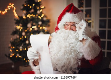 Santa Claus reading from a long list, in a cozy room