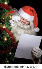 Santa Claus reading wish list beside Christmas tree