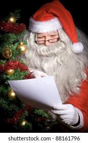 Santa Claus reading wish list beside Christmas tree at night. Giving away Xmas gifts.