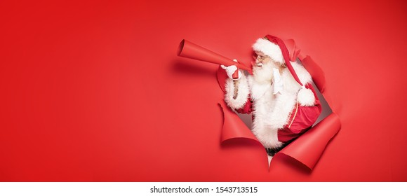 Santa Claus , the real one, comes out of the red studio background , screaming ho ho ho through big megaphone. Christmas time.