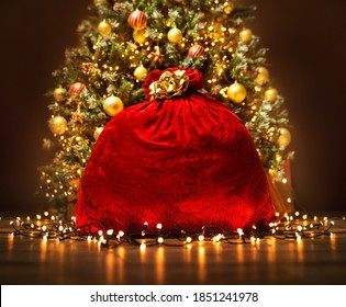 Santa Claus Red Bag full with Toy Gifts, Christmas Presents. Christmas Sack tied by Golden Bow Ribbon over Decorated lightening ChristmasTree in dark Room