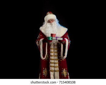 Santa Claus in a red fur coat, with a white beard presents gifts from a bag on a black background