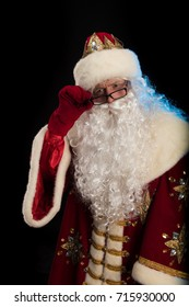 Santa Claus in a red fur coat, with a white beard and glasses on a black background