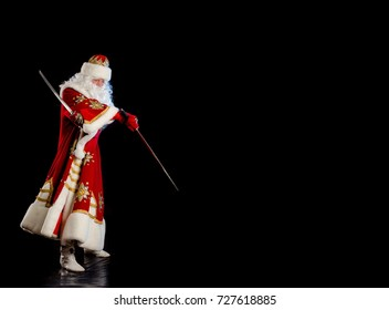 Santa Claus in a red fur coat, with a white beard with two swords in his hands, posing on a black background
