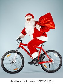 Santa Claus with red sack riding bicycle