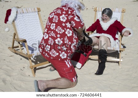 5ef02358 Santa Claus in red swimming trunks and Hawaiian shirt on sandy beach  helping to remove Mrs