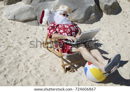 cb1d00e1 Santa Claus in red swimming trunks ans Hawaiian shirt lounging on sandy  beach with straw hat