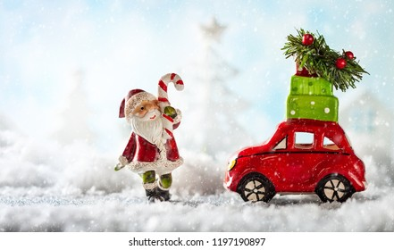 Santa Claus and red toy car carrying Christmas gifts in snowy landscape. Christmas concept with copy space.
