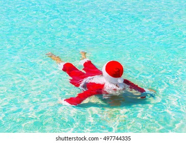 Santa Claus relax swimming in ocean turquoise azure transparent water, Christmas and New Year holidays travel destinations in hot countries concept