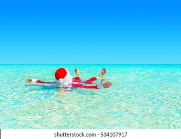 Santa Claus relax swimming in ocean turquoise transparent water. Merry Christmas and Happy New Year travel destinations concept.