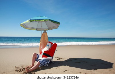 Santa Claus relaxes on his Lounge Chair with his Surf Board, under his beach umbrella at the beach with the beautiful blue ocean in the background. Focus on Santa's Face. Santa Vacation.