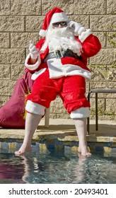 Santa Claus relaxing by the swimming pool while talking on the phone and enjoying an alcohol beverage