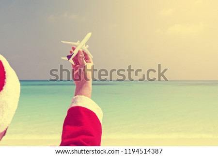 Santa Claus Relaxing At Chaise Longue And Holding Airplane Model In Hand On Sea Background With