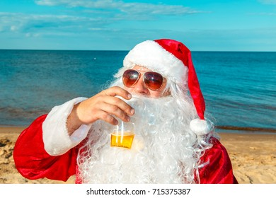 Santa Claus is resting on the beach with beer.