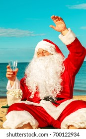 Santa Claus is resting on the seashore with beer and popcorn.