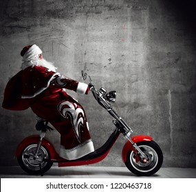 Santa Claus ride motorcycle bicycle scooter with bag full of present gifts with text copy space. New year and Merry Christmas and happy holidays concept