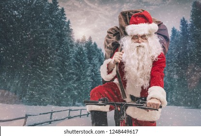Santa Claus riding a bicycle and carrying a heavy sack with gifts for Christmas under the snow