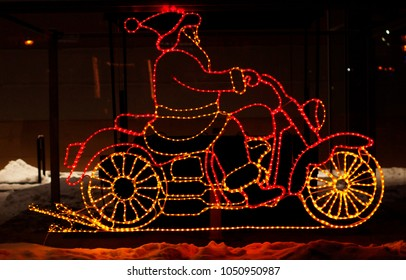 santa claus is riding a motorcycle made from garlands