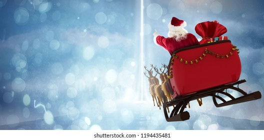 Santa Claus riding on sled with gift box against street leading against cloudy sky
