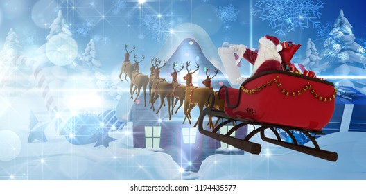 Santa Claus riding on sled during Christmas against christmas house with gifts and candy canes