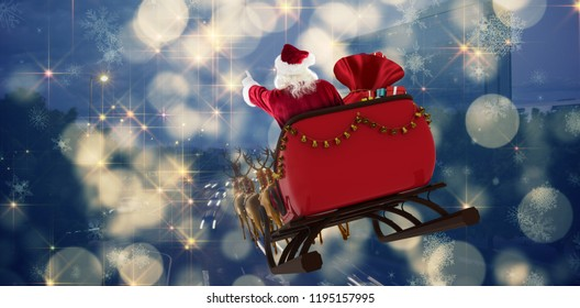 Santa Claus riding on sled with gift box against cars moving on road in city at night