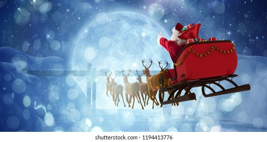 Santa Claus riding on sleigh with gift box against bridge on snow covered mountain against full moon