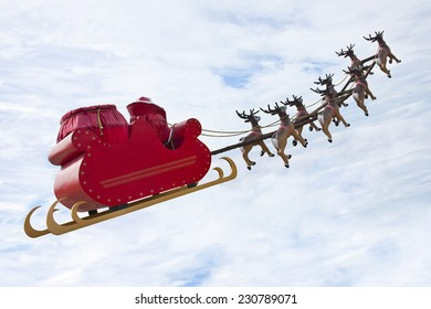 Santa Claus riding a sleigh in a day light led by reindeers