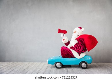 Santa Claus riding toy car. Senior man speaking into megaphone. Christmas Xmas holiday concept