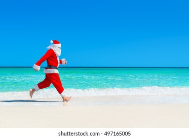 Santa Claus run at tropical sea beach sand against waves splashes, Christmas and New Year's travel destinations concept