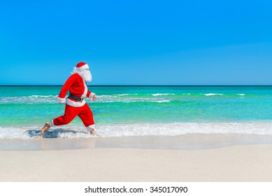 Santa Claus running at sandy tropical sea beach on waves foam splashes, Christmas and New Year's vacation in hot countries concept