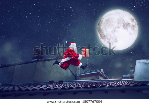 Santa Claus runs fast on a roof with a present