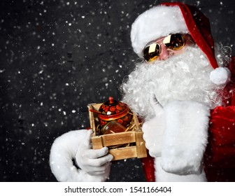 Santa Claus s holding wooden crate with a jar of red salmon caviar and showing thumb up sign gesture on dark. New year and Merry Christmas and happy holidays concept