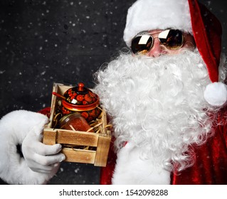 Santa Claus s holding wooden crate with a jar of red salmon caviar and can with traditional painting decoration on dark. New year and Merry Christmas and happy holidays concept