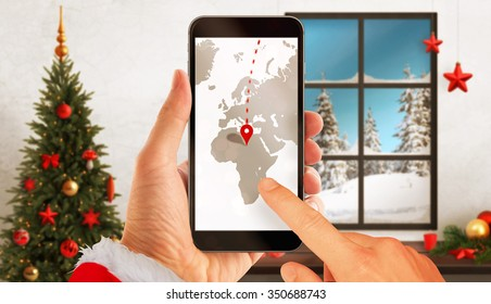 Santa Claus search the route on the map over the phone to deliver gifts. Christmas tree, gifts, decorations in background.