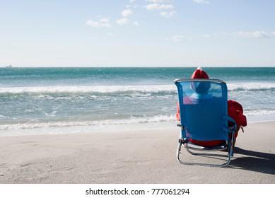 santa claus, seen from behind, sitting in a deckchair on the beach facing the horizon