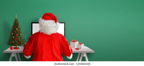 Santa Claus send letters online. Christmas tree, gifts and decorations on work desk. Green wall in background with copy space.