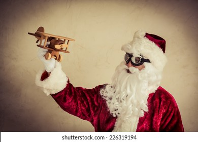 Santa Claus senior man playing with vintage wooden airplane against grunge background. Xmas holiday and winter vacation concept