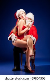 Santa Claus with sexy girl in Santa hat.