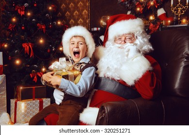 Santa Claus and shouting cute boy sitting in Christmas room with gifts. Christmas home decoration.