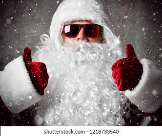 Santa Claus show thumbs up under snow confetti. New year and Merry Christmas and happy holidays concept