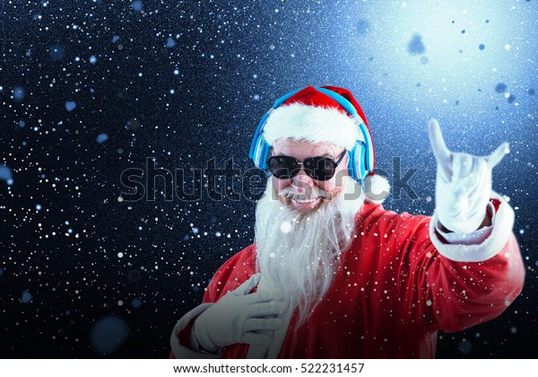 Santa claus showing horn sign while listening to music on headphones against snow with red flakes