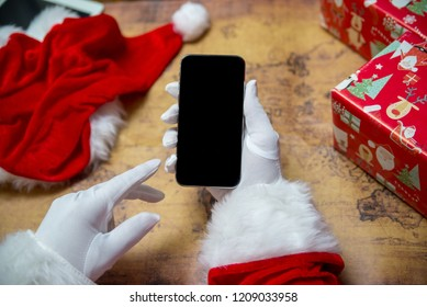 Santa Claus showing using mobile phone on festive background. Closeup shot elderly person with digital gadget, technology copyspace wireless wishlist concept. top side view old adult social post idea