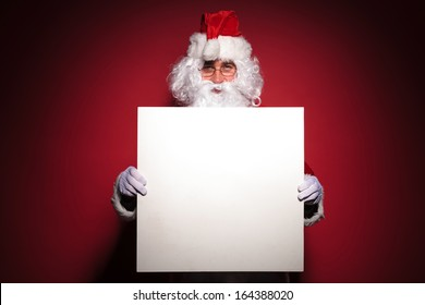 santa claus showing you a blank sign on a red background