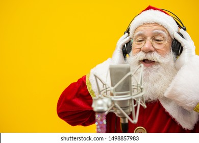 Santa Claus singing or speaking in a studio microphone. Merry Christmas. Broadcaster. Announcer. Promotion. Christmas music concept.