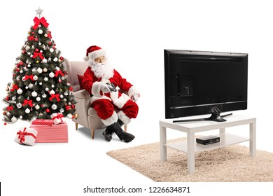 Santa Claus sitting in an armchair, holding a remote controller and watching TV isolated on white background
