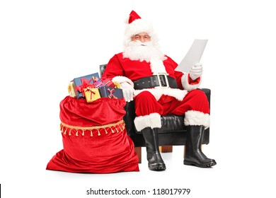 Santa Claus sitting in armchair and reading a letter next to a bag full of gifts isolated on white background
