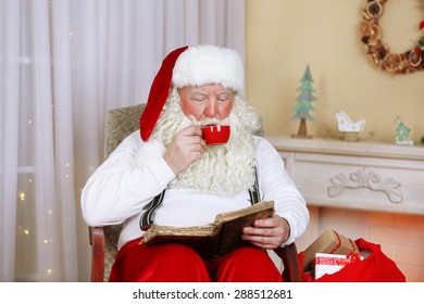 Santa Claus sitting with book in comfortable chair near fireplace at home